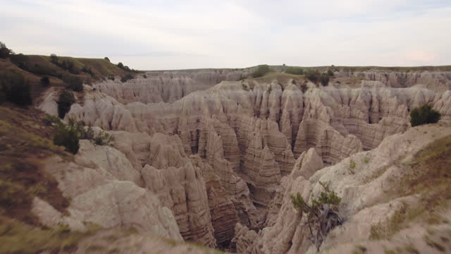 drone. epic aerial view over badlands rock formations towards steep prehistoric canyons - badlands national park video stock e b–roll