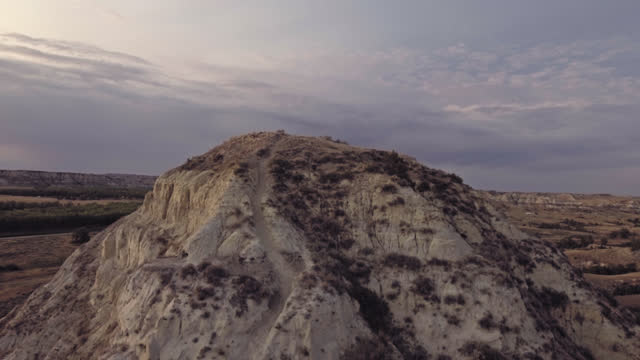 drone. epic aerial view rising over grassy plateau revealing prehistoric landscape of badlands formations - badlands stock videos & royalty-free footage