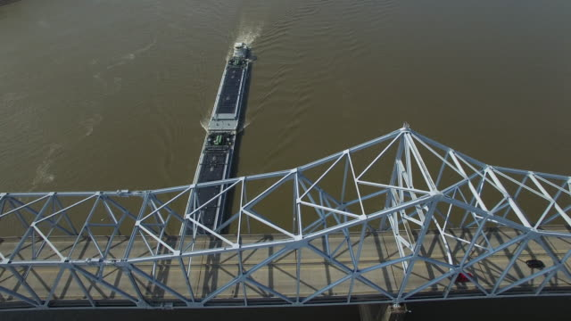 Epic backwords tracking of barge over bridge reveal river - Drone Aerial 4K Mississippi river bridge and barge 1of14, everglades, gulf delta, new orleans, st louis, with cruise boats sailing and wildlife 4K Transportation