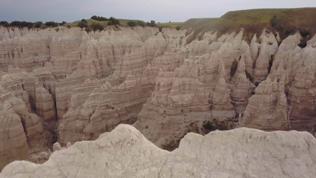 drone. epic erial view of badlands formations passing ove majesticr high peaks towards green plateaus - badlands national park video stock e b–roll