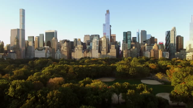 vídeos de stock, filmes e b-roll de epic establishing shot of new york city skyline and central park at sunset - inclinação para cima