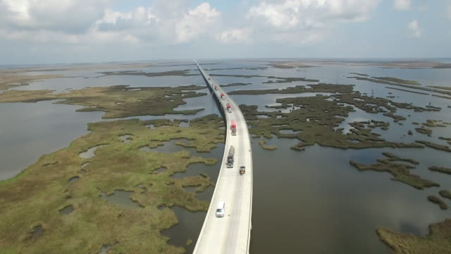 epic long backwords tracking of trucks on causeway - drone aerial 4k lake pontchartrain causewaygrand isle louisiana coast mississippi river bridge and barge everglades, gulf delta, with wildlife 4k transportation - louisiana stock videos & royalty-free footage