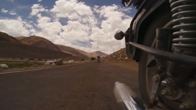 epic reverse view of royal enfield motorcyclists driving through mountain landscape in leh, india - royal blue stock videos & royalty-free footage