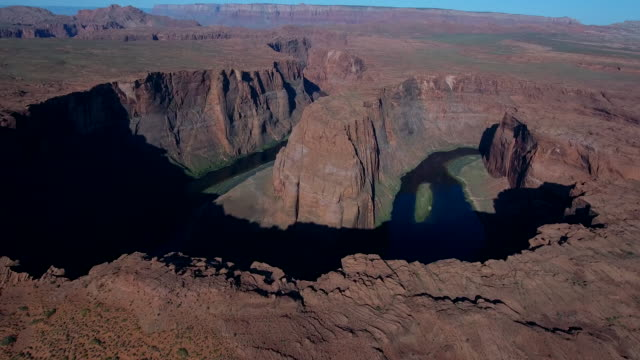 epic short pan up of horseshoe bend 4k, drone aerial view of horseshoe bend along the colorado river leading to grand canyon and glen canyon. morning and evening light with sun on the horizon - grand canyon stock videos and b-roll footage