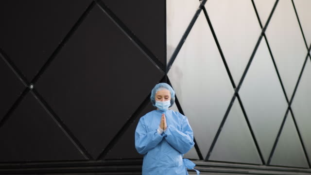 epic shot of female doctor or nurse praying in medical mask and surgical cap - surgical cap stock videos & royalty-free footage