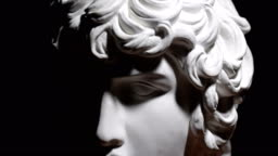 Epic studio close-up  shot of a gypsum head with moving and changing lighting. The play of light and shadow on half the face of a white statue of a man. On a black background isolated 4k