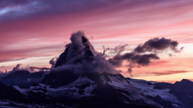 epic sunset timelapse shot of the matterhorn with fiery clouds and lights on the ascent route - mountain stock videos & royalty-free footage