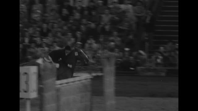 equestrian rider and horse jump over two obstacles on course in show jumping event at summer olympics / gv horse jumps obstacle on course in olympic... - 1956 bildbanksvideor och videomaterial från bakom kulisserna