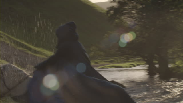 equestrians riding through a forest stream. - hood clothing stock videos & royalty-free footage