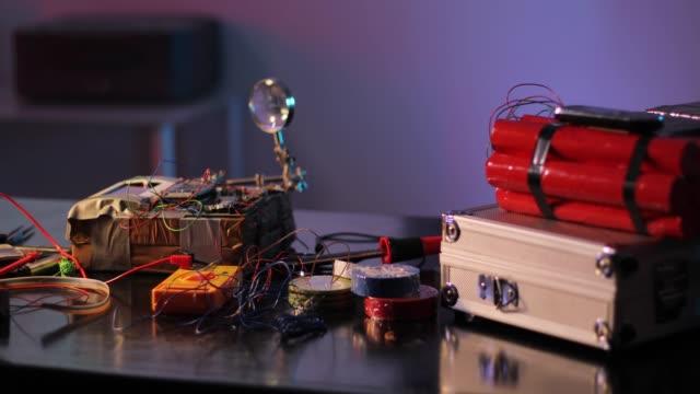 vídeos y material grabado en eventos de stock de equipo para la construcción de bombas sobre mesa en el taller terrorista - haz de luz