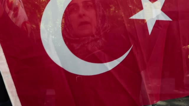 erdogan supporters gather outside chatham house ahead of a visit by the turkish president recep tayyip erdogan on may 14, 2018 in london, england. mr... - トルコ国旗点の映像素材/bロール