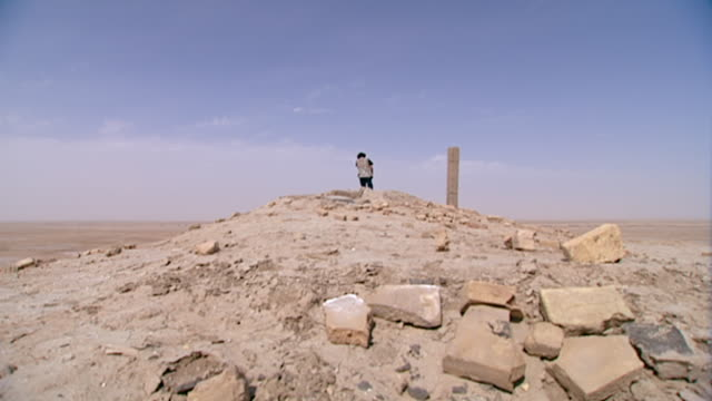 eridu, tell abu shahrain. view of a man descending from the top of the ruins of eridu, considered the oldest city on earth founded circa 5400 bce. - basra stock-videos und b-roll-filmmaterial