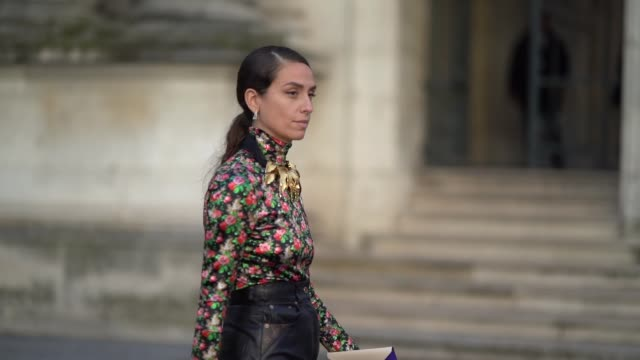 erika boldrin wears a golden necklace with attached parts shaped as leaves a multicolor floral print turtleneck top a black leather skirt green shoes... - floral pattern stock videos & royalty-free footage