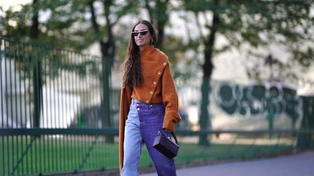 vídeos de stock e filmes b-roll de erika boldrin wears an orange oversized pullover, blue flare jeans, a black bag, outside koche, during paris fashion week womenswear spring/summer... - jeans