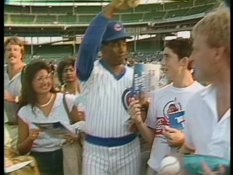 ernie banks with baseball and pen in hand walks with fans on the field - sport stock-videos und b-roll-filmmaterial