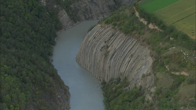 vídeos de stock, filmes e b-roll de aerial ws eroded rock formation along river drac / rhone-alpes, france - erodido
