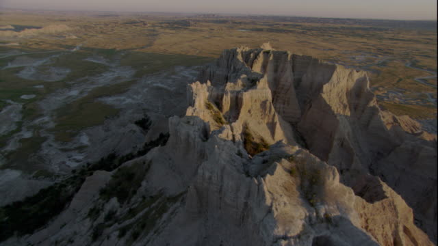 eroded rock formations tower in the middle of an arid canyon. available in hd. - badlands national park stock videos & royalty-free footage