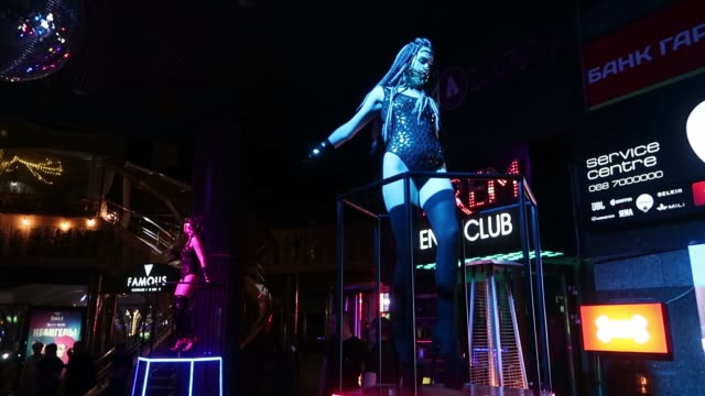 erotic dancers dancing at the entrance to a nightclub which offers a striptease program near bessarabska square in the city of kiev ukraine - tänzerin stock-videos und b-roll-filmmaterial