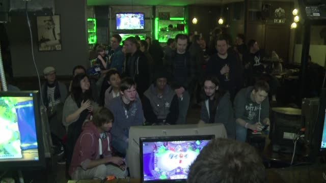 es sabado por la noche en un abarrotado pub de londres y la multitud disfruta de una partida de videojuego que se proyecta en una gran pantalla en... - multitud stock videos & royalty-free footage