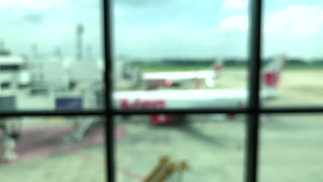 escalator moving forward in airport terminal and blurred plane in background - stair lift stock videos and b-roll footage