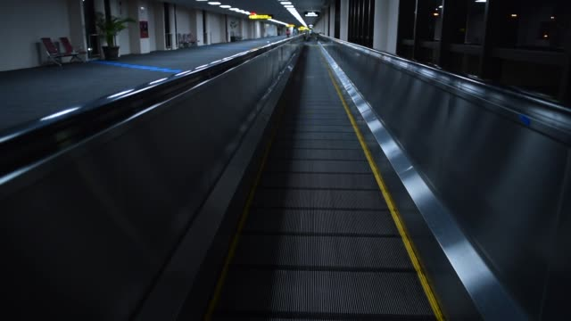 escalator moving forward in airport terminal at night - stair lift stock videos and b-roll footage