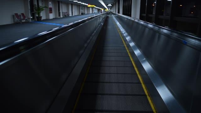 vidéos et rushes de escalator, aller de l'avant dans le terminal de l'aéroport de nuit - se déplacer vers le bas