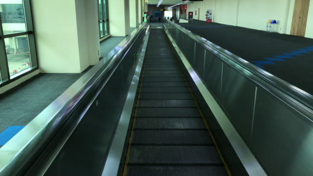 escalator moving forward in airport terminal - stair lift stock videos and b-roll footage