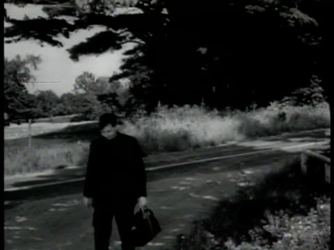 stockvideo's en b-roll-footage met escaped nazi prisoner hitchhiking on road ms prisoner being dropped off in forestarea vs walking pass fence underbrush vs fbi agents following nyc - 1942