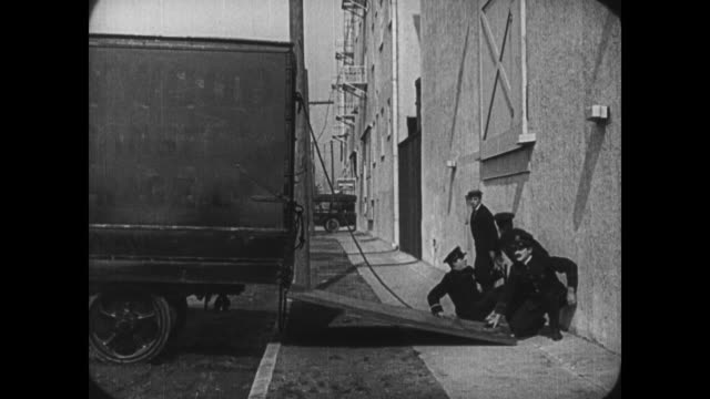 vidéos et rushes de 1921 escaping man (buster keaton) alludes police tail by tricking officers into back of truck until they fall back out right in front of him - exploit sportif