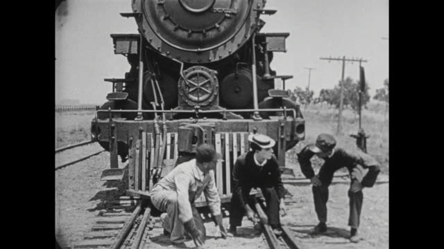 1922 escaping man (buster keaton) almost gets hit by train - dragging stock videos & royalty-free footage