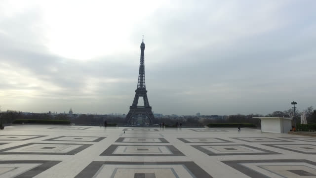 esplanade du trocadero with very very few people with the eiffel tower in the background president macron invokes war as europe goes dark in... - eiffelturm stock-videos und b-roll-filmmaterial