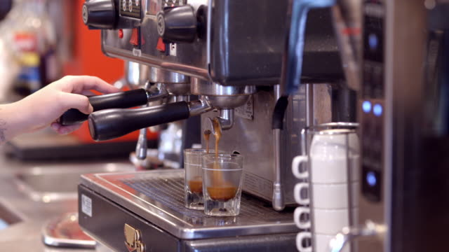vídeos de stock e filmes b-roll de ecu espresso machine brew flows into shot glasses removed by barista hands when full / redlands, california, usa - cafeteria