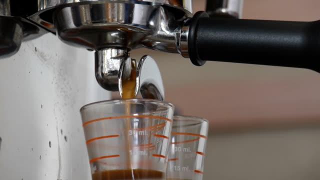 Espresso machine pouring into two shot glasses