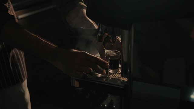 espresso poured into glass from espresso machine in modern coffee shop - etwas herstellen stock-videos und b-roll-filmmaterial