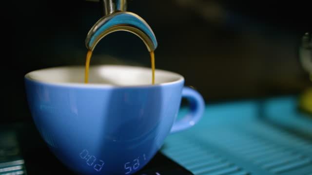 espresso gießt von beiden seiten eines espressomaker spout und in einen kleinen blauen kaffeebecher in einem coffee shop - ausgusstülle stock-videos und b-roll-filmmaterial