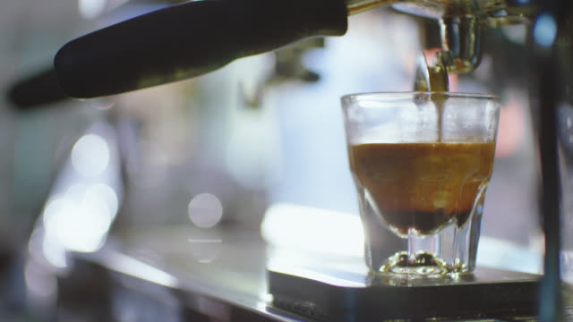 CU. Espresso pours into glass from espresso machine in modern coffee shop.