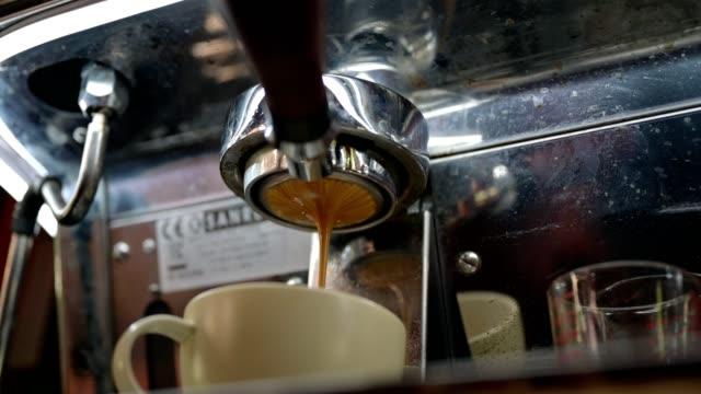 ボトムレスポルタフィルターからコーヒーカップに注ぐエスプレッソショット - エスプレッソ点の映像素材/bロール