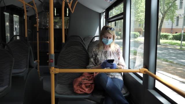 vídeos de stock e filmes b-roll de essential worker in public transportation during coronavirus pandemic, using phone for communication - epidemiologia
