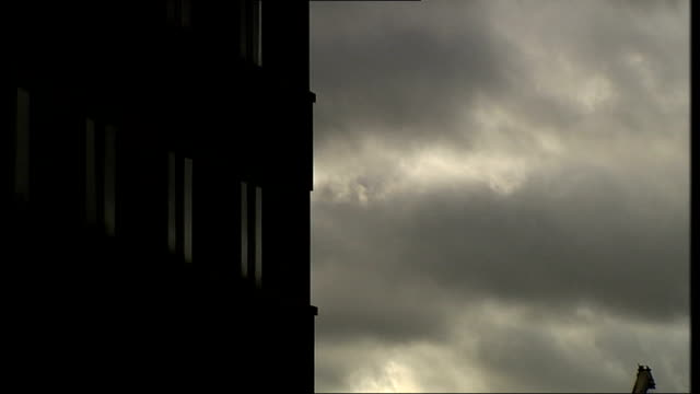 silhouette of hospital building against dark clouds - basildon stock-videos und b-roll-filmmaterial
