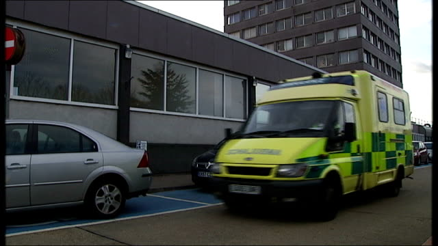 sign for 'basildon university hospital' over entrance, ambulance along and silhouette of hospital building against dark clouds - basildon stock videos & royalty-free footage