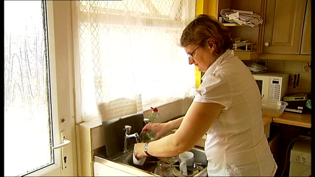 essex grandmother becomes michael jackson impersonator; england: essex: basildon: int christine guntrip washing dishes guntrip polishing kitchen... - basildon stock videos & royalty-free footage