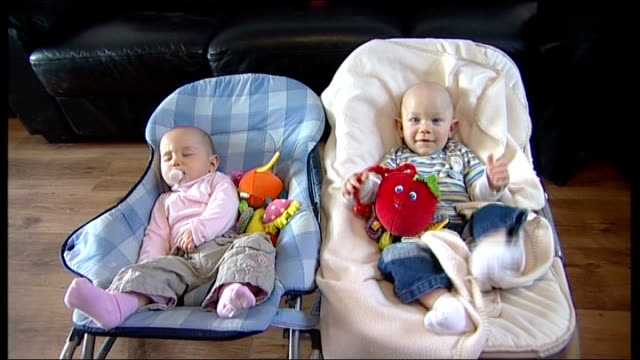 essex int superfetation babies thomas and harriet mullineux in bouncy chairs thomas rocking in his chair harriet looking at reflecting toy both... - dondolarsi video stock e b–roll