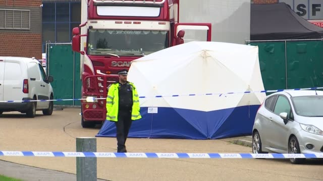 crime scene gvs; england: essex: grays: waterglade industrial park: ext police officer standing guard by tape cordon and fence / lorry behind fence... - エセックス州点の映像素材/bロール