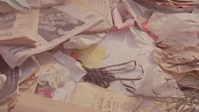 est. garbage dump; close on trash; 2 - taped sticks of dynamite (1 - lit) tossed onto pile 1/2 way thru shot - dynamite stock videos & royalty-free footage