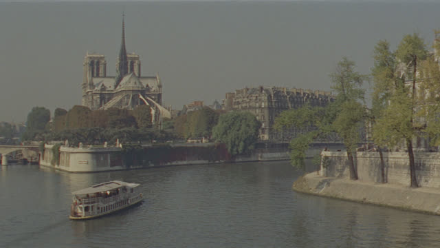 est. paris, river seine; buildings & cathedral in b.g., riverboat away from camera on river - establishing shot stock videos & royalty-free footage
