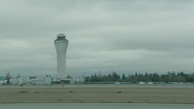 vídeos de stock e filmes b-roll de est. seattle-tacoma airport, control tower prominent, passenger jet taxi r-l - torre de controlo de tráfego aéreo