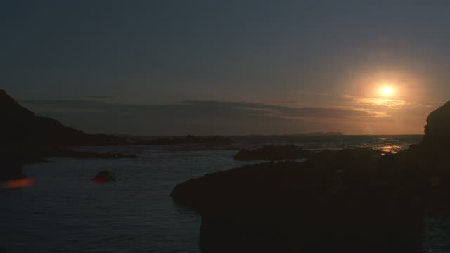 establish sunset over ocean/rocky coastline in foreground - horizon over water stock videos & royalty-free footage