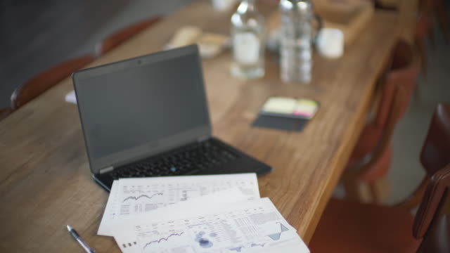 establisher shot of an open laptop on a table with charts - 空白の画面点の映像素材/bロール