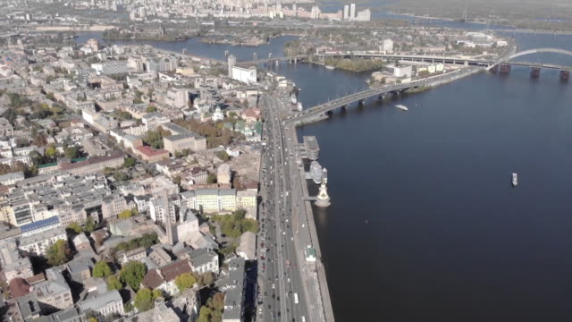 vídeos de stock e filmes b-roll de establishing aerial drone reveal shot over naberezhnokhreshachatyts'ka street and the dnieper river in kiev ukraine - aerial or drone pov or scenics or nature or cityscape