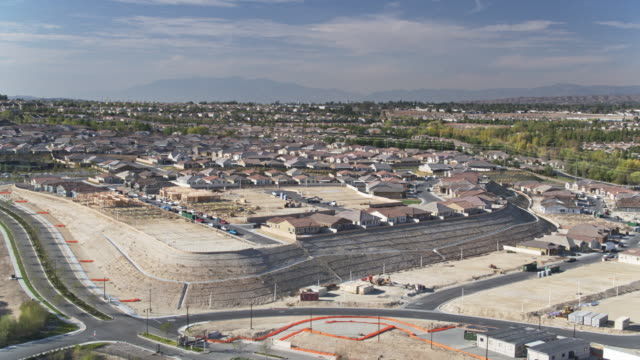 establishing aerial shot of a suburb bordered by ongoing construction - riverside california stock videos and b-roll footage